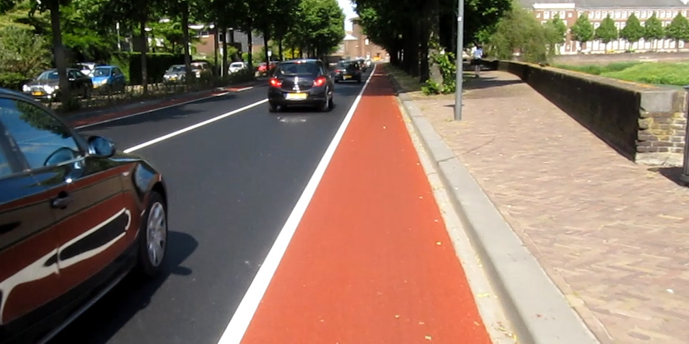 After: very smooth new asphalt with a bright red cycle lane.