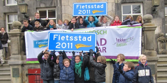 "School children with the award on the steps of city hall: signs with the title ""Cycling City 2011"""