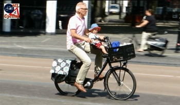 A grandfather cycling with his grandchild.