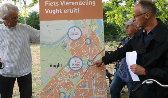 A representative of the local chapter of the Cyclists' Union pointing at a portable map to make the consequences of the plans clear.