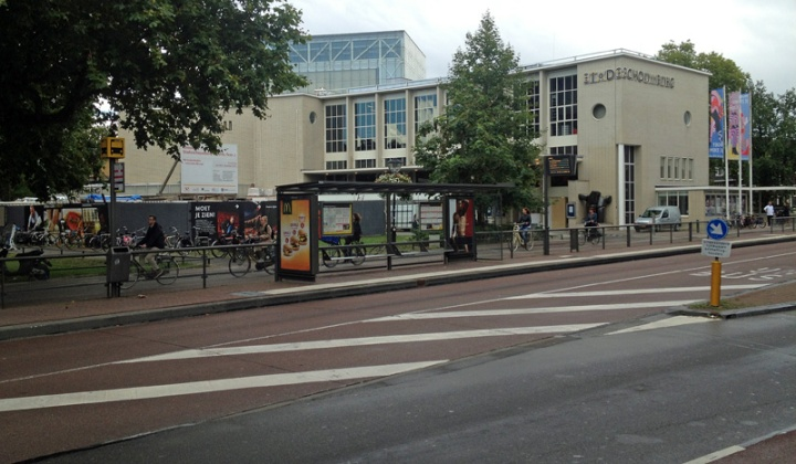The city theatre in 2015. The street has become a bus lane and behind the bus stop shelter people cycle on a very wide cycleway.