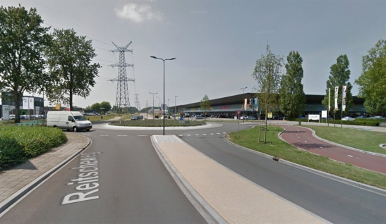 The connection Reitscheweg - Aziëlaan has become a roundabout for motor traffic that is by-passed by a bi-directional cycleway. A re-located parking-lot access makes it a four-arm roundabout where there was only a T-junction before.
