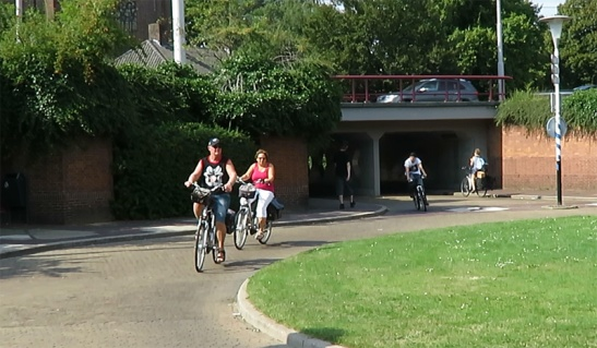 People cycling in the lower level - the 'Bear pit' of the Arnhem Airborneplein.