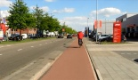 This man passes a commercial driveway. The continuous design of the cycleway makes clear that the people passing it in a motor vehicle must give way to this man on his bicycle.