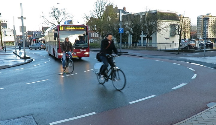 A bus / bike conflict at the canal ring. The main cycle route is straight on while the main route for motor traffic turns.