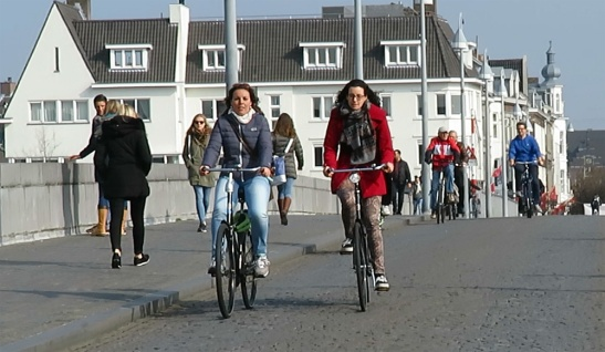 Cycling on the old bridge over the river Meuse (Maas) in Maastricht.