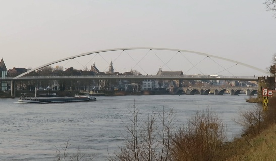The arch of the cycle bridge over the Meuse river. In the distance the old bridge. A bridge was first built by the Romans, but this version dates back to the 13th century.
