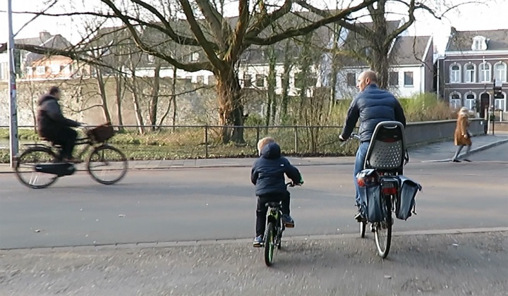 A father teaching his son to look left before crossing this street just outside the historic city centre of Maastricht.