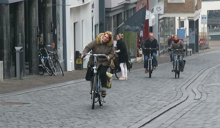 This woman is strugling to cycle up the hill in the historic city centre. She manages! The woman in the background has a much easier task: she rides an e-bike.