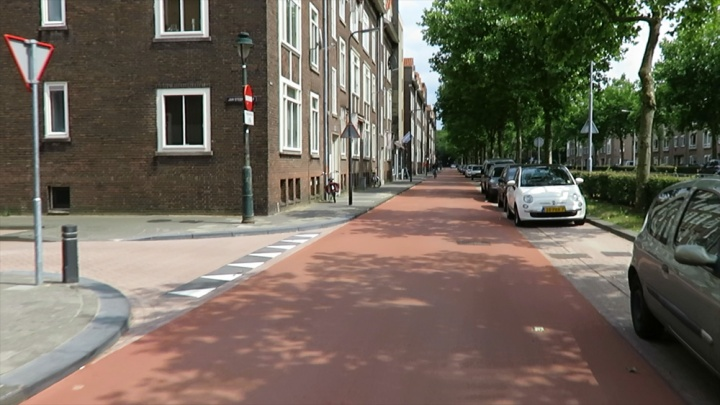 The service street has become a cycle street where cars are guest. The street now has priority over side streets and the line of parked cars has shifted to the other side. Combined with the one-way regime, this means that dooring is virtually impossible now (parked cars face arriving cyclists).