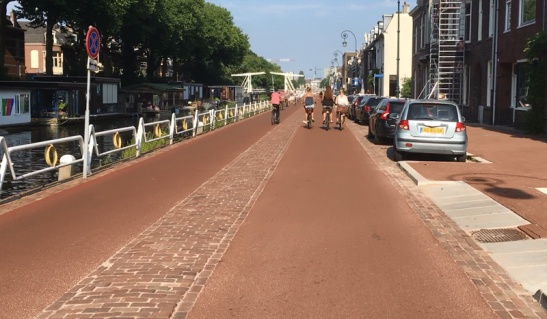The same location in 2016 with the smooth red asphalt for more comfortable cycling. There is a mountable median that suggests 2-way traffic, but that is not the case. Cars are only allowed in one direction, cycling is allowed in both directions.