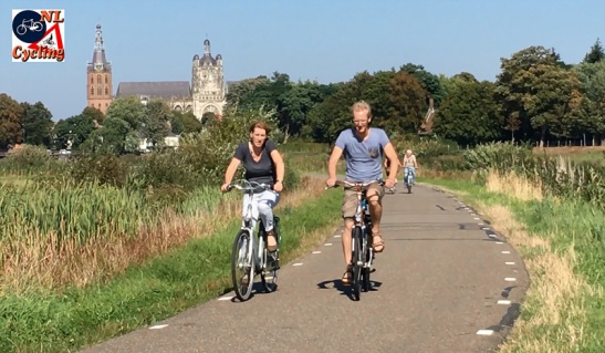 Cycling with the 's-Hertogenbosch cathedral in the background.