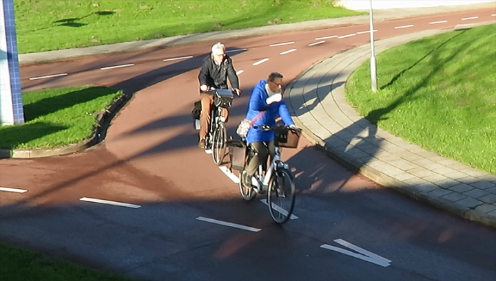 An elderly couple cycle at Tiendenplein in Goes, at the bottom of a raised roundabout.