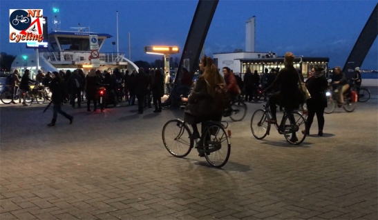 A bicycle/pedestrian ferry arriving at the shared space ferry terminal behind Amsterdam Central Station in the evening.